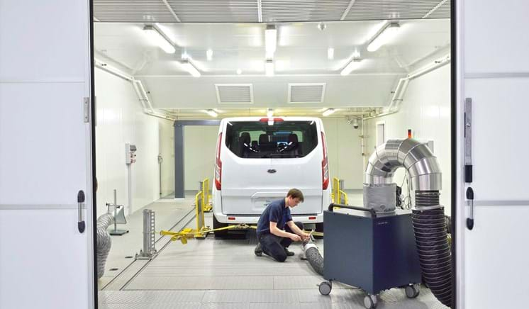 Vehicle emissions test engineer working on a van in a 4WD chassis dyno facility at Millbrook Proving Ground