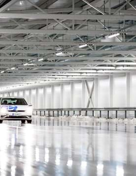 Car driving on ice in indoor winter test facility with cold-weather vehicle tracks at Test World in Ivalo, Finland