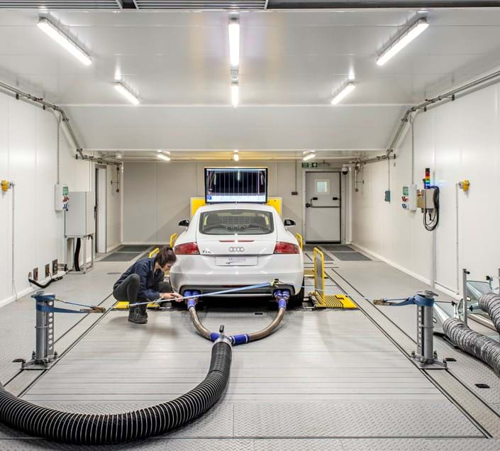 Engineer working on a car in a 4WD climatic chassis dynamometer emissions test facility at Millbrook Proving Ground