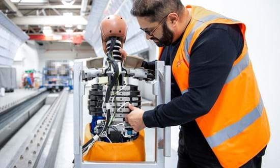 Millbrook engineer setting up dummy for rail vehicle passenger seat testing